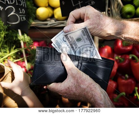 Human hand holding the money and spending goods