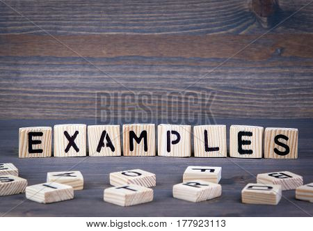 Examples word written on wood block. Dark wood background with texture.