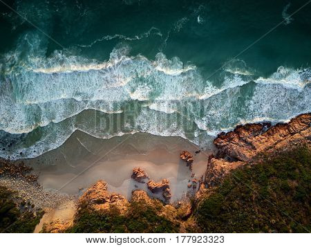 Small waves repeatedly crashing on small sandy shore bay beach with rough rocky coastline, aerial photography overhead