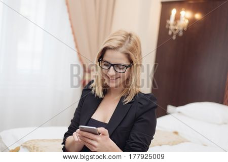 Good business talk. Cheerful young beautiful woman in glasses texting on mobile phone