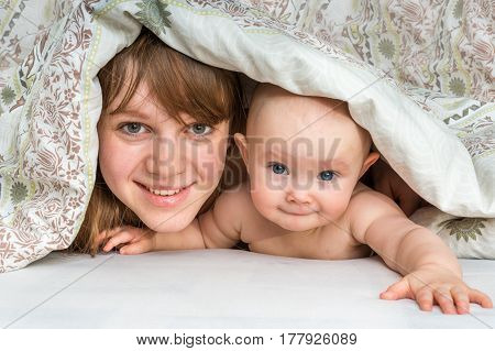 Mother And Her Baby Playing And Smiling Under A Blanket