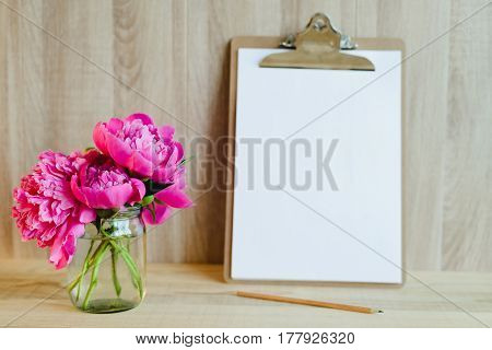 blank clipboard with pencil and pink peony bouquet in wooden interior
