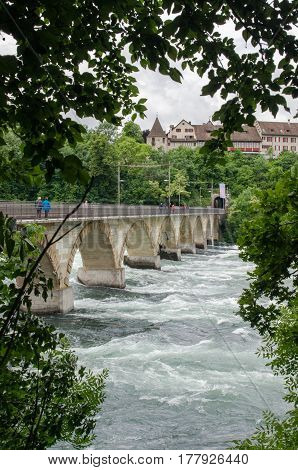 Tourist walks on bridge near Rheinfall largest plain waterfall in Europe