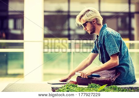 Male fashion student concept. Guy holding notebook wearing jeans outfit and eccentric sunglasses sitting on white ledge next to modern building