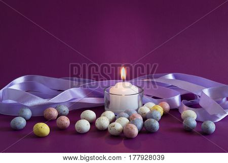 Violet Easter egg background with lit candle and small speckled chocolate eggs - with lilac satin ribbon