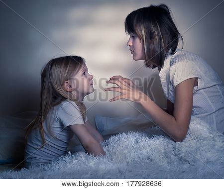 story before bed. Older sister tells younger sister a scary story