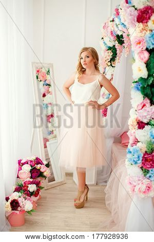 Young blonde pretty woman near bed decorated with flowers.