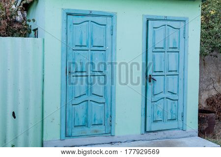 Public toilet doors painted in blue. The door on the left with the symbol