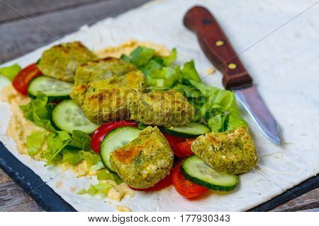 Green open falafel with hummus and vegetables on pita bread on slate and dark background. Love for a healthy vegan food concept