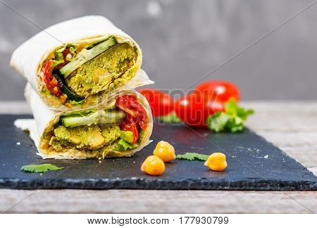 Green falafel with hummus and vegetables in pita bread on a slate and dark background. Love for a healthy vegan food concept