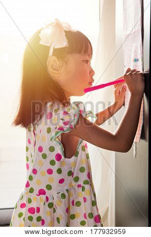 Asian Chinese Little Girl Writing On Paper With  Back Lighting