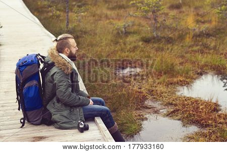 Bearded man sitting in swamps and enjoying the views. Camp, adventure, traveling and trip concept.