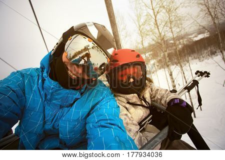 Dad with his daughter skiers on the ski lift