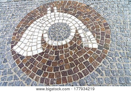 The emblem of The emblem of a post office (post horn) in the form of a mosaic on the sidewalk. Austria Tyrol Mayrhofen.