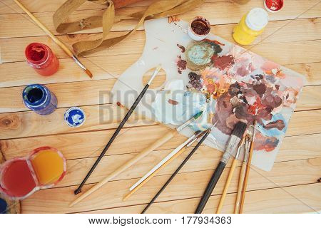 The artist's palette. Colored oil paints over a pallete on a table
