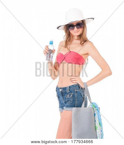 Pretty girl posing in bikini, summer hat and sunglasses, with bag and bottle of water, isolated on white background