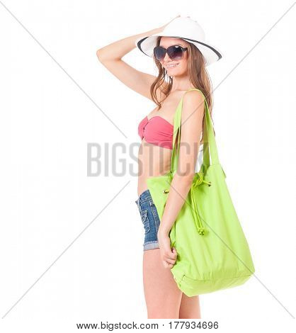 Pretty girl posing in bikini, summer hat and sunglasses, with bag, isolated on white background