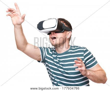 Amazed man wearing virtual reality goggles watching movies or playing video games gesticulating hands, isolated on white background. Surprised male looking in VR glasses.