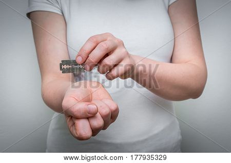 Unhappy woman committing suicide with a sharpened razor