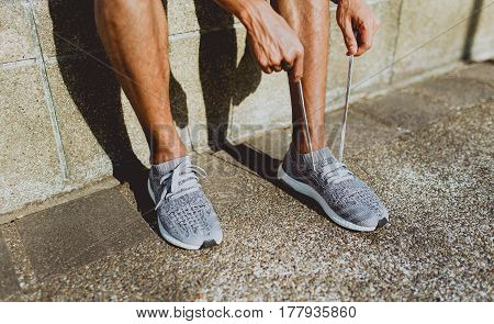 Runner tying shoelace getting ready for run. selective focus on hand.