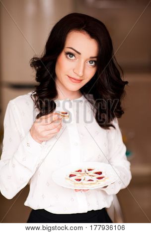 Smiling woman 24-29 year old holding heart shaped cookies on white plate in kitchen. Looking at camera. Bakery.