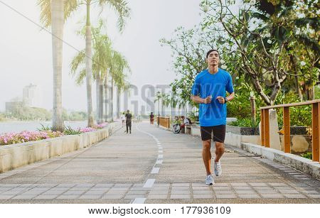 Running man. Male runner jogging during outdoor workout at public park.