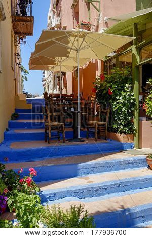 terrace with chairs tables and umbrellas on a stairway in a narrow street on the island of Crete Greece