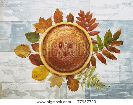 pie on wooden background and autumn leaves