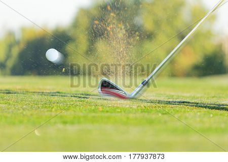 Chipping a golf ball onto the green with golf club, close-up.