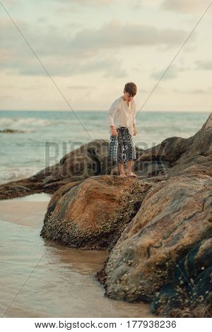 A hot day in the ocean, a cute, barefooted boy stands on large stones