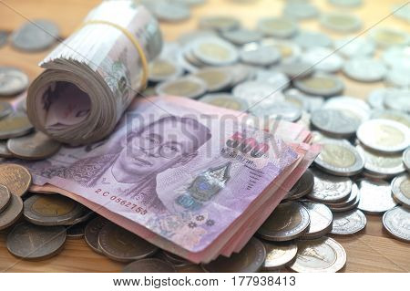 thai baht currency saving banknote and coins on wood table.