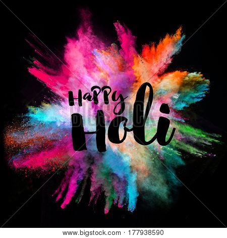 Colored powder explosion on black background. Happy Holi concept.