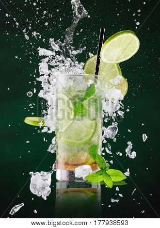 fresh mojito drink with liquid splash and crushed ice in freeze motion, close-up.