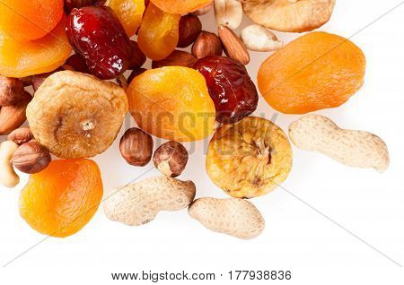 Dried fruits dates lemon apricots figs and nuts on a white background.