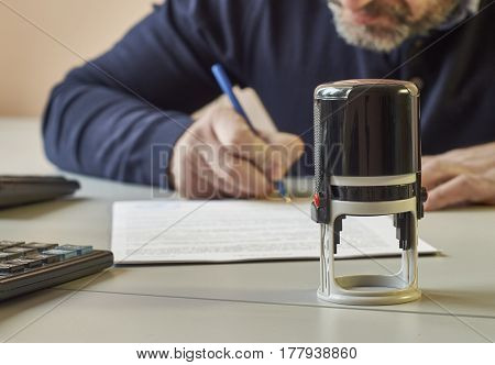 Middle-aged businessman sitting at office desk and signing a contract