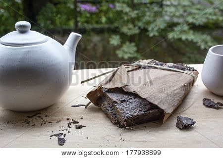 Black natural tea with white teakettle and a cup on the wooden table and green leaves as background