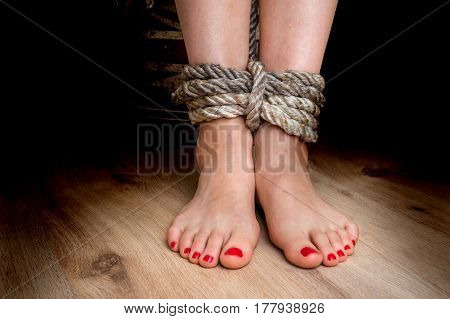 Female legs tied with rough rope - violence concept