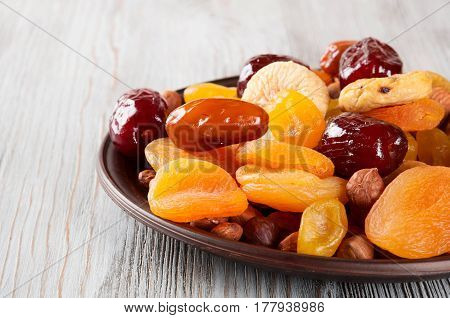 Dried fruits on a wooden background. Dates lemon apricots figs and nuts in a clay plate.