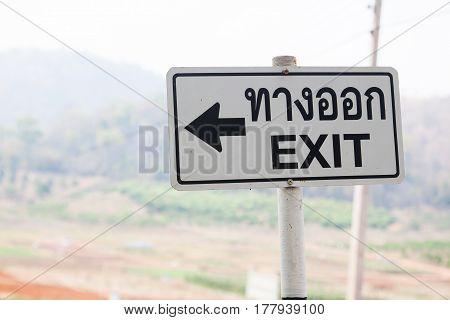 Exit signage in farm with mountain background