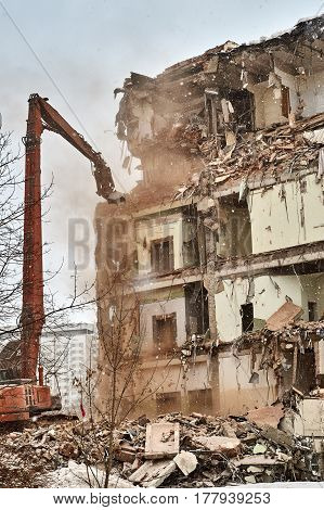 Builders demolishes a city house using an excavator equipped with special hydraulic scissors