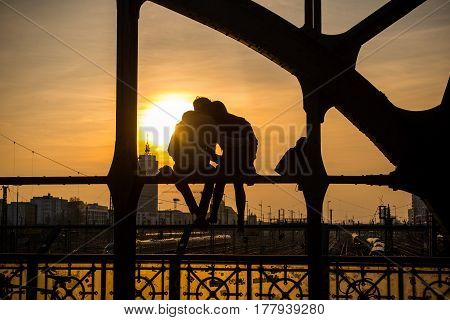 Munich,Germany-March 23,2017: A couple watches the sunset from a bridge over the railroad tracks