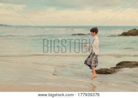 A hot day a little boy on the ocean jumps on the beach
