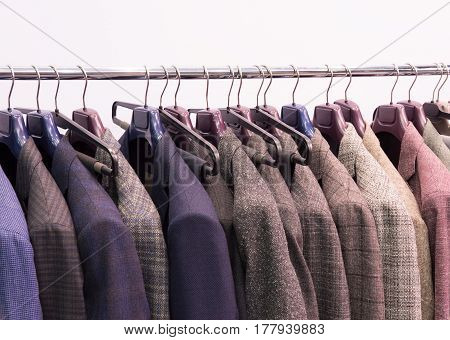 Men trousers and jackets on hangers in the shop. Selective focus.