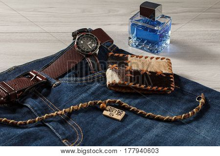 Man perfume watch with a leather strap blue jeans with leather belt leather purse and amulet on a gray wooden background
