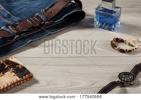 Man perfume watch with a leather strap blue jeans with leather belt amulet and leather purse on a gray wooden background
