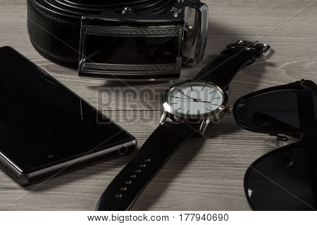 Watch with a leather strap leather belt with metal buckle sell phone black sunglasses on a gray wooden background