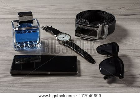 Man perfume watch with a leather strap leather belt with metal buckle sell phone black sunglasses on a gray wooden background