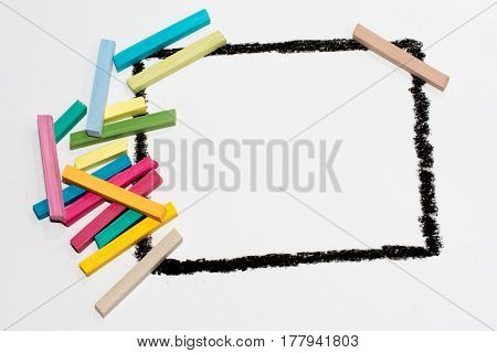 The black frame on a white background, painted wax crayons on the edges of multicolored chalk. Children's creativity. Colorful chalk. Space for text, letters, words. Education, to develop the child.