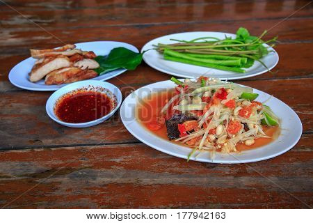 Famous Thai food, papaya salad or SOM TAM or Somtum. on wooden table.