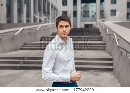 Handsome young man walking in an urban street. Young man in white shirt standing near the business center.